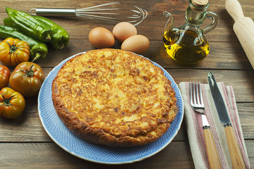From above plate with typical Spanish omelette, oil, cookware and fresh vegetables on wooden table.
