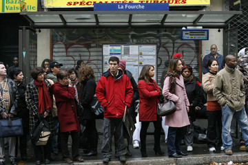 Commuters wait for a bus at La Fourche bus station in Paris