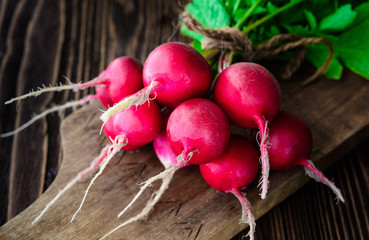 Bunch of fresh radish on wooden background and cutting board
