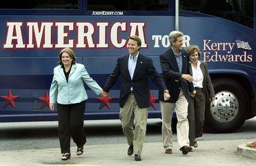 Democratic presidential nominee Kerry and running mate Edwards walk by bus.
