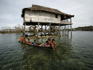 Children from Indonesia's Bajo tribe sit in a wooden boat near their home on Wanci island in Sulawesi province