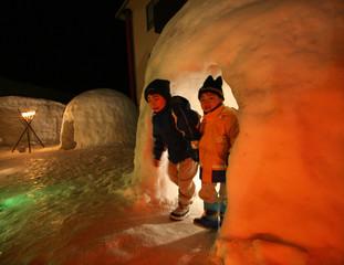 Japanese boys peek out from snow hut in Myoko north of Tokyo