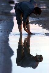 SYRIAN MAN STANDS IN A FLOODED VILLAGE AFTER DAM BURST IN ZEYZOUN.