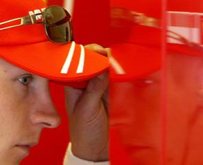 Ferrari Formula One driver Raikkonen of Finland adjusts his cap