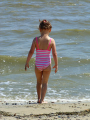 The baby in a swimsuit is standing by the water