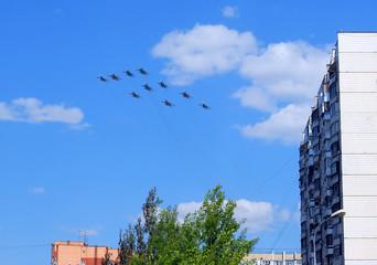 Группа из многофункциональных истребителей-бомбардировщиков Су-34, многоцелевых всепогодных истребителей Су-27 и многоцелевых сверхманёвренных истребителей Су-35с в небе над жилыми домами