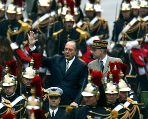 French President Jacques Chirac waves to crowds as he rides in his military command car down the Cha..