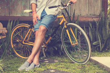 Hipster man with old bicycle.