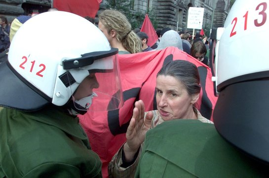 A MIDDLE AGED WOMAN TRIES TO PASS BETWEEN GERMAN RIOT POLICE AND ANTIMILITARY DEMONSTRATORS IN BERLIN.