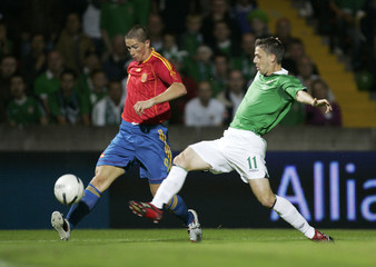 Spain's Torres is tackled by Northern Ireland's Baird during their Euro 2008 Group F qualifying match at Windsor Park