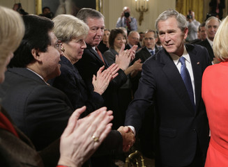 U.S. President George W. Bush shakes hands with former Attorney General Gonzales after his final prime time speech at the White House in Washington