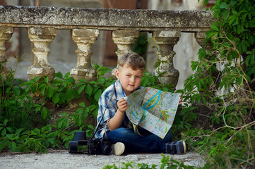 boy with retro camera and city map