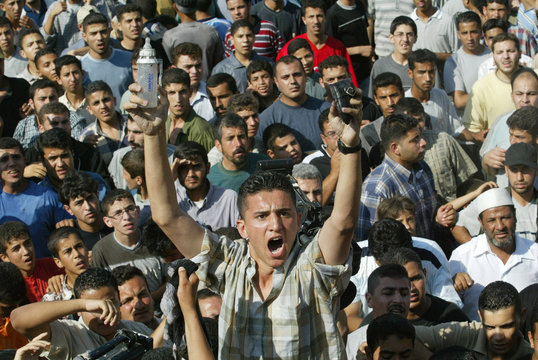 AN ANGRY PALESTINIAN YOUTH HOLDS UP A BABY'S BOTTLE AND SHOE AFTER ANISRAELI HELICOPTER STRIKE IN ...