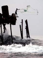 Guatemalan fisherman casts his net into sea churned up by tropical storm Adrian in Puerto San ...