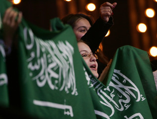 Saudi Arabians hold flag as they celebrate the victory of singer al-Hakami in televised contest in Beirut