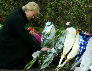 OAKE THE WIDOW OF MURDERED DC OAKE LOOKS AT FLOWERS AT THE MURDER SCENEIN MANCHESTER.