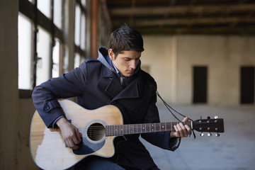 Young musician. Shot of a young musician playing his acoustic guitar.