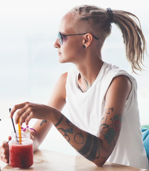 Young woman with dreadlocks sitting in cafe drinking smoothie
