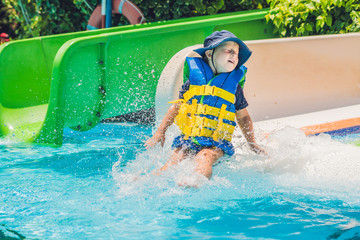 Foto op Aluminium Amusementspark A boy in a life jacket slides down from a slide in a water park