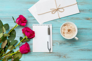 Morning coffee, roses and a notebook for notes on a turquoise wooden background. Top view with space for text.