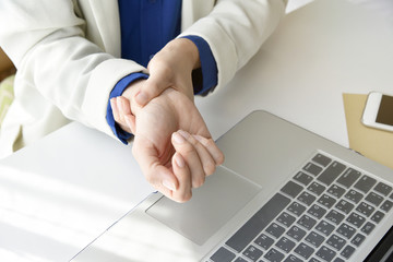 Office syndrome hand pain by occupational disease, Closeup business woman with wrist pain, Woman holding her wrist pain from using computer.