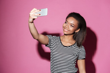 Portrait of a happy young african woman taking selfie