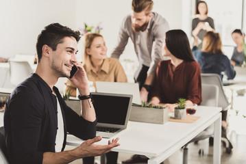 Smiling office worker speaking on phone