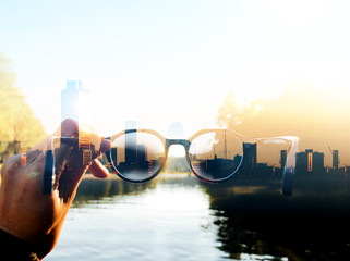 Double exposure image of Hand-held glasses scene is Cityscape focus, Business vision