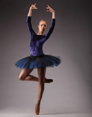 Young and incredibly beautiful ballerina in blue outfit is posing and dancing in studio. classical ballet art. on one leg