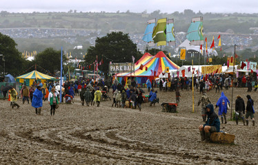 Revellers walk through a muddy field during the Glastonbury music festival in Somerset