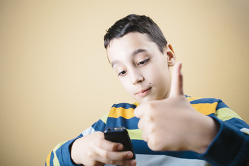 Boy with cellphone showing you thumbs up.