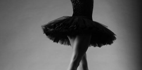 unrecognizable ballerina in studio, black tutu. classical ballet art. black and white image, body part