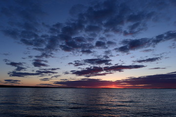 Flash of a bright red sunset on the horizon in the sky above the lake