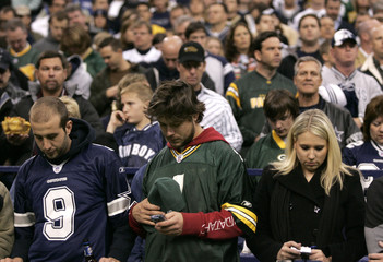 Green Bay Packers and Dallas Cowboys fans pause for a moment of silence in Irving