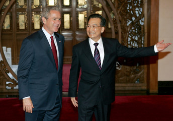 Chinese Premier Wen Jiabao shows the way to U.S. President George W. Bush in Beijing