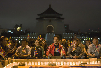 Tibetans and activists pray during a night vigil in Taipei