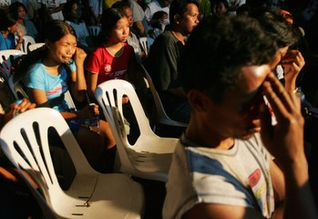 Evacuees of the buried Guinsaugon village in central Philippines grief at a mass