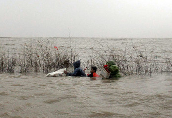 Fishermen collect clams to save them from being washed away from rising sea water caused by Typhoon Kaemi at fishing pond place in Fuzhou