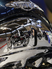 Motorcycles are reflected in the fuel tank of a Triumph Rocket during the International Motorcycle and Scooter show in Birmingham