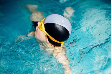 Little cute boy learning to swim in sport pool. Swimming school for small children. Healthy kid enjoying active lifestyle.