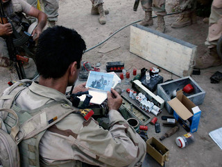 Iraqi soldiers look at bomb-making equipment found in garden after raid on outskirts of Baquba