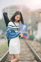 Girl with a guitar standing on railway tracks .