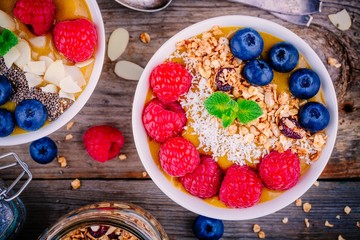 Peach smoothie bowls with raspberries, blueberries, chia seeds and granola
