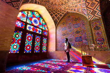 An asian female tourist facing the multicolors light through spectacular stained glass in Nasir Al-Mulk Mosque (Pink Mosque) in Shiraz - Iran.