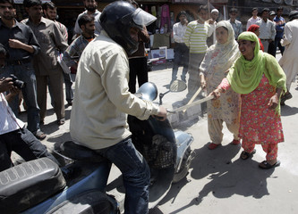 Kashmiri woman stops a two wheeler during a protest in Srinagar