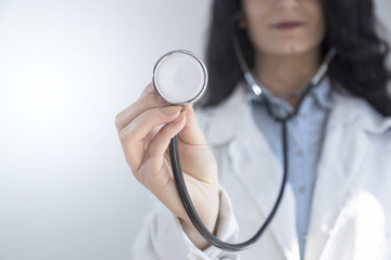 Close up of female doctor in white gown with stethoscope, focus on stethoscope. White background.
