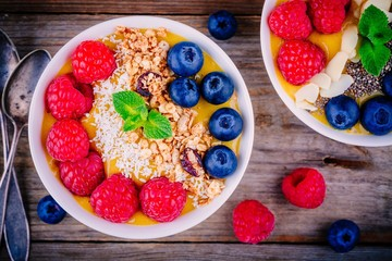 Mango smoothie bowl with raspberries, blueberries, granola and coconut