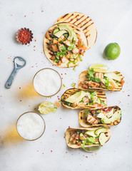 Healthy corn tortillas with grilled chicken, avocado, fresh salsa, limes, beer in glasses over light grey marble background, top view. Healthy food, gluten-free, weight loss, allergy-friendly concept