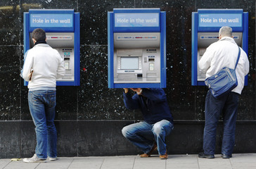 A man repairs a cash machine outside a bank in London