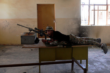 A sniper from Iraqi Army aims at Islamic State positions from a school building on the frontline during clashes in north west of Mosul